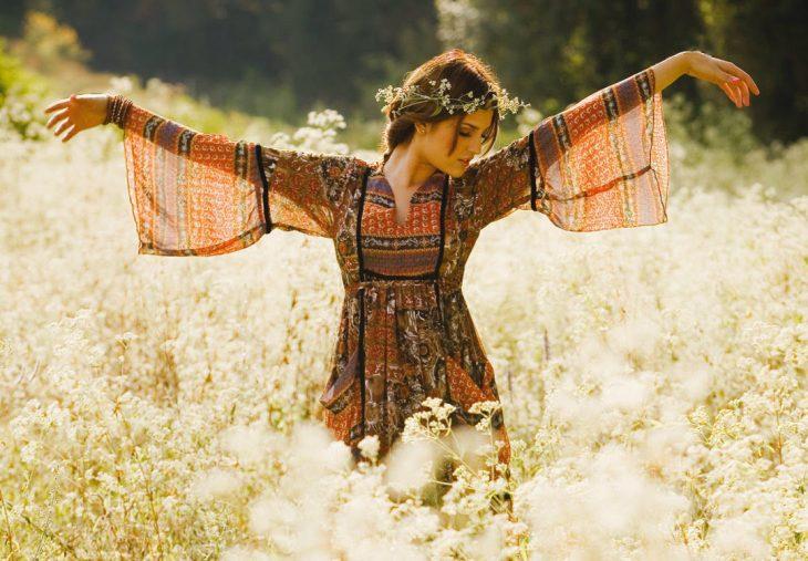 Chica con los brazos extendidos meintrás se encuentra en medio de un jardín