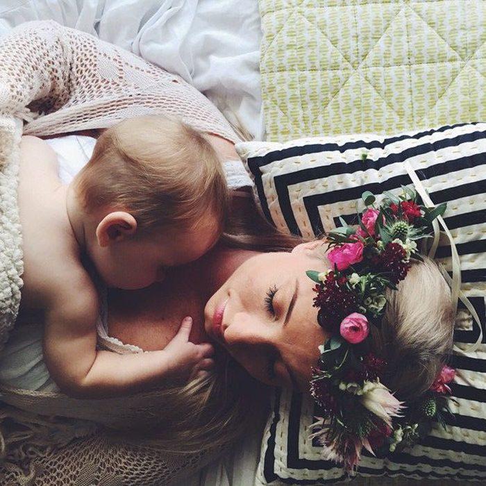 madre acostada con corona de flores y su bebé en el pecho