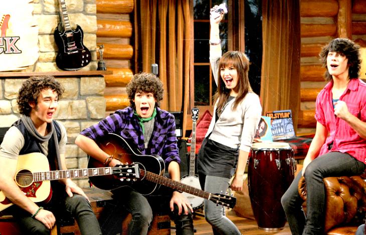 chicos con gitarras y chica sonrie en una cabaña camp rock