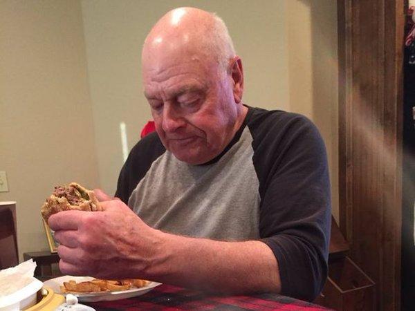Abuelo triste comiendo una hamburguesa mientras está solo