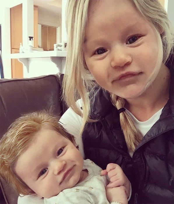 Bebé con demasiado cabello intercambiando el rostro con su madre