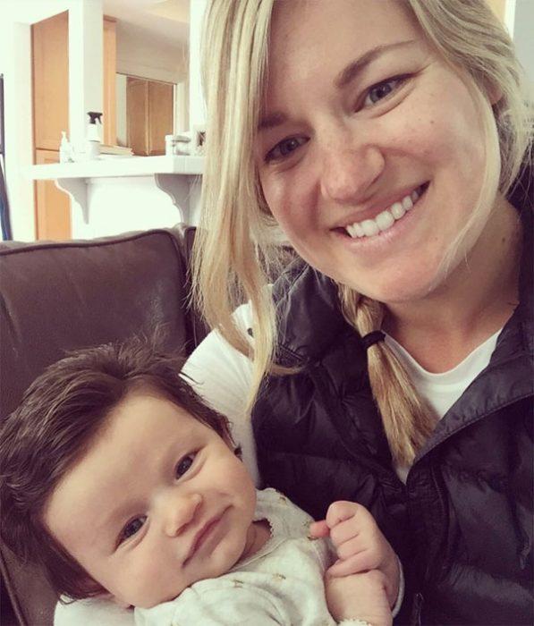 Bebé Isabelle con demasiado cabello siendo sostenida por su madre