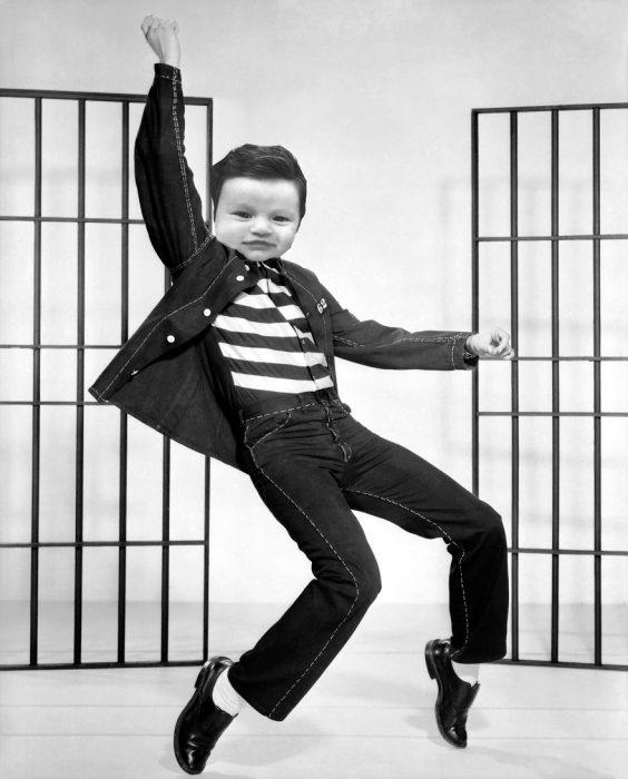 Bebé con demasiado cabello luciendo igual que Elvis presley bailando el rock de la cárcel