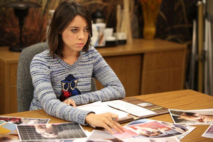 Chica sentada frente a un escritorio con cara de molestia