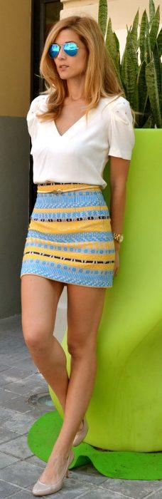 Chica recargada sobre una pared verde usando una falda amarilla con azul y una blusa blanca