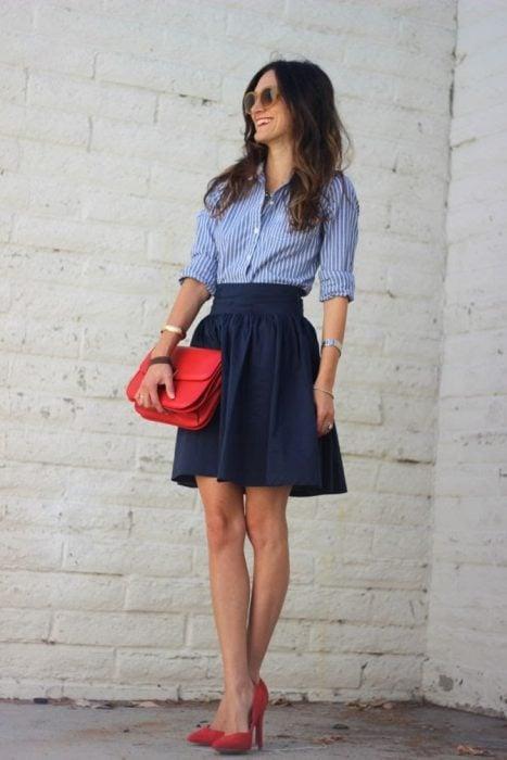 Chica usando una blusa azul con lineas verticales y una falda color azul marino, bolso y zapatos rojos