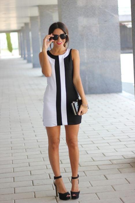Chica bajita usando unos zapatos negros con correas en los tobillos