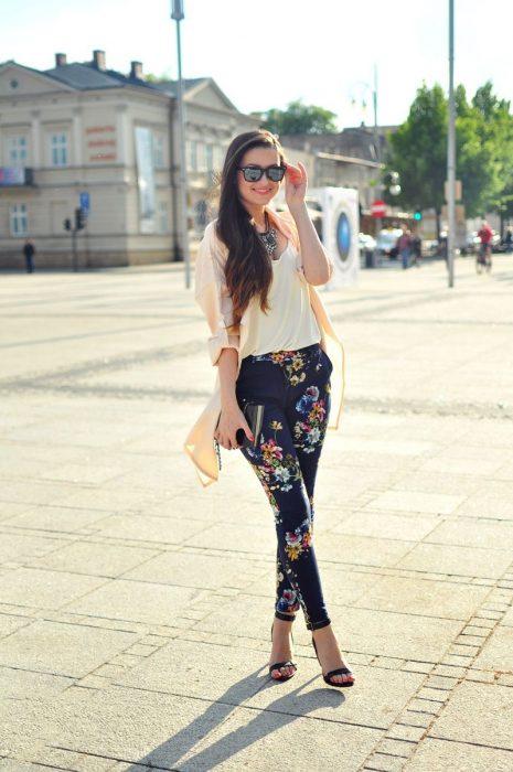 Chica parada en una plaza usando un pantalón con flores y una blusa color beige