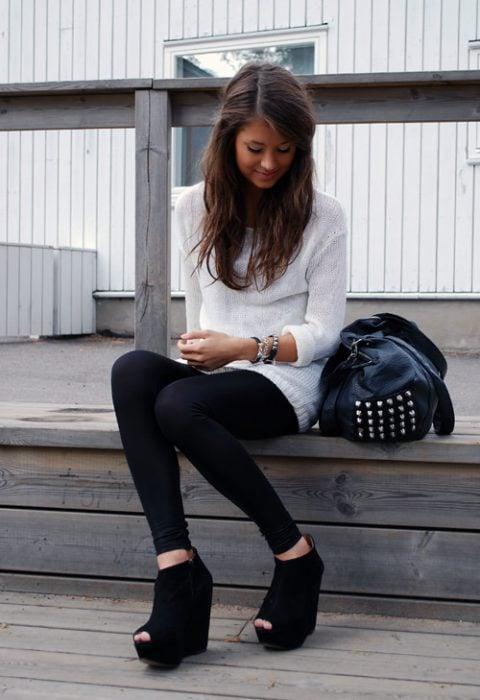 Chica sentada en un pórtico usando unas zapatillas de tacón corrido