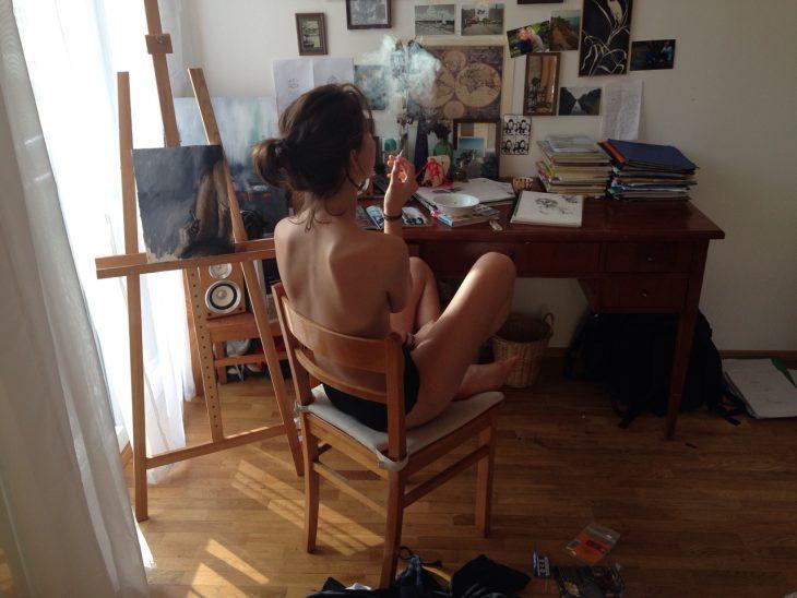 Chica fumando mientras pinta