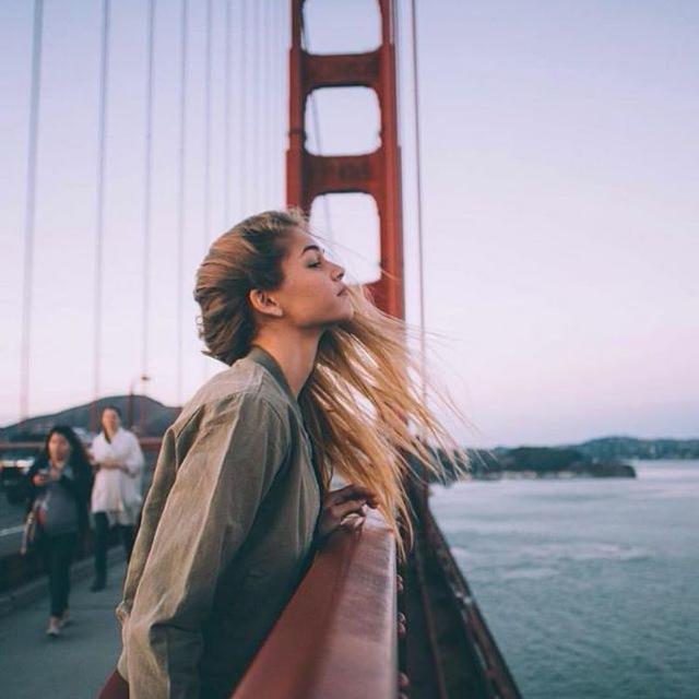 Chica recargada en un puente