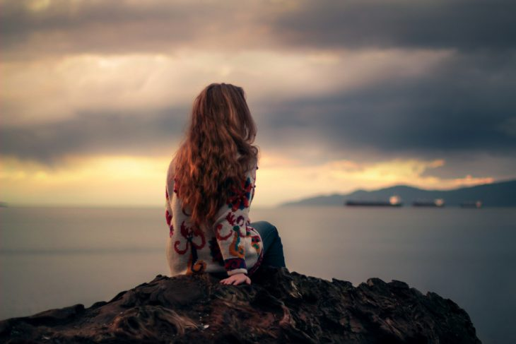 Chica pensando frente a la playa