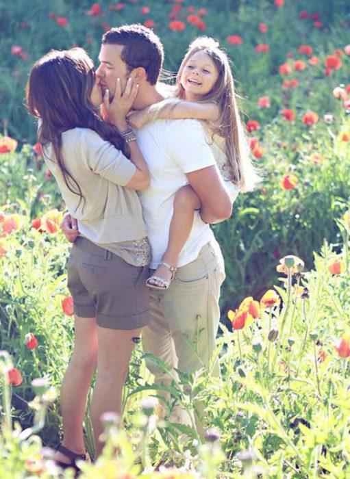 Pareja de novios besándose mientras sostienen a una bebé