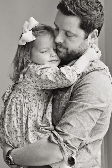 Padre sosteniendo a su hija en brazos mientras la abraza contra su pecho