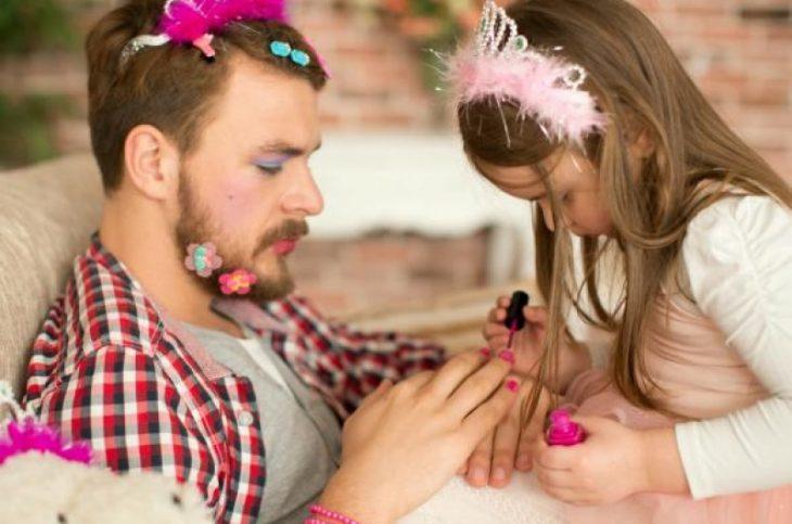 Padre jugando con su pequeña hija mientras le pinta las uñas de color rosa