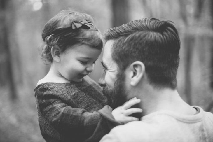 Padre sosteniendo a su hija en brazos mientra la mira de frente
