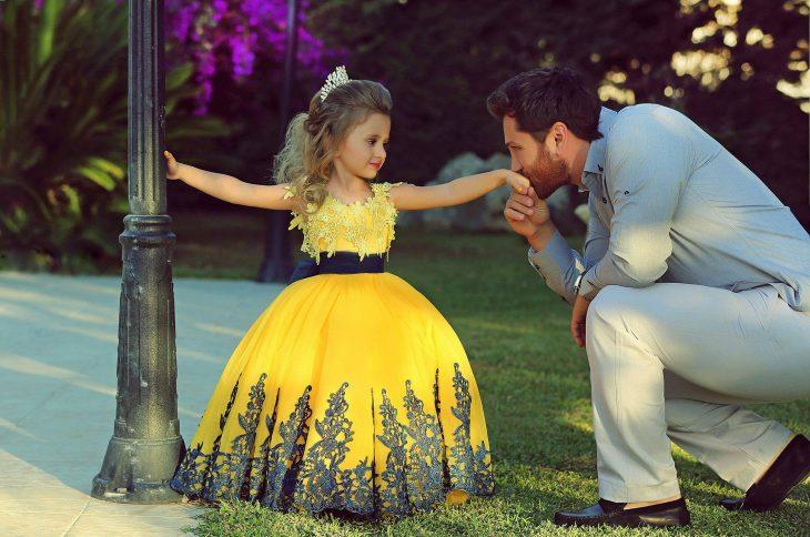 Padre besando la mano de su pequeña hija vestida de princesa