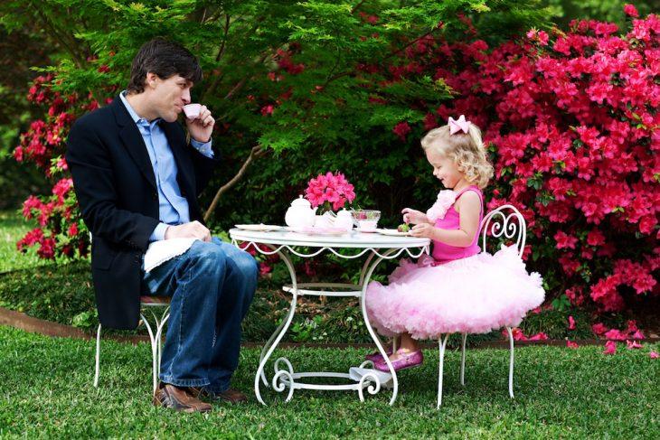 Padre e hija tomando el té mientras están en el jardín