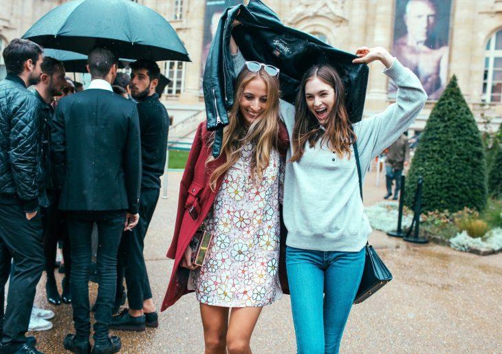 Amigas sonriendo bajo la lluvia