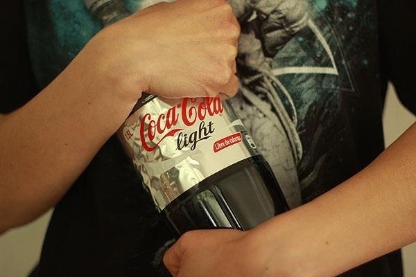 mujer abrazando una botella de coca cola light
