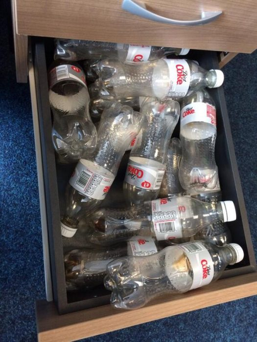 cajón de escritorio con botellas vacías de coca cola