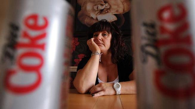 mujer pensativa entre latas de coca cola light
