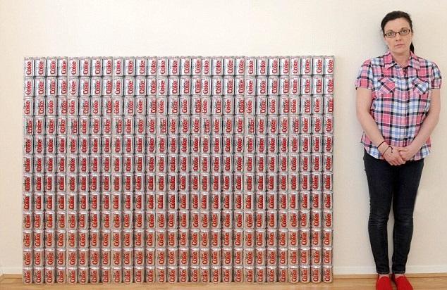 mujer con pared de latas de refresco