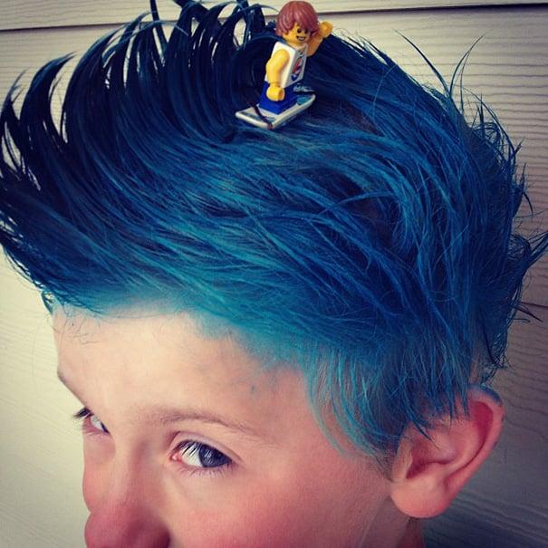 Niño con el cabello color azul simulando un surfista en una ola