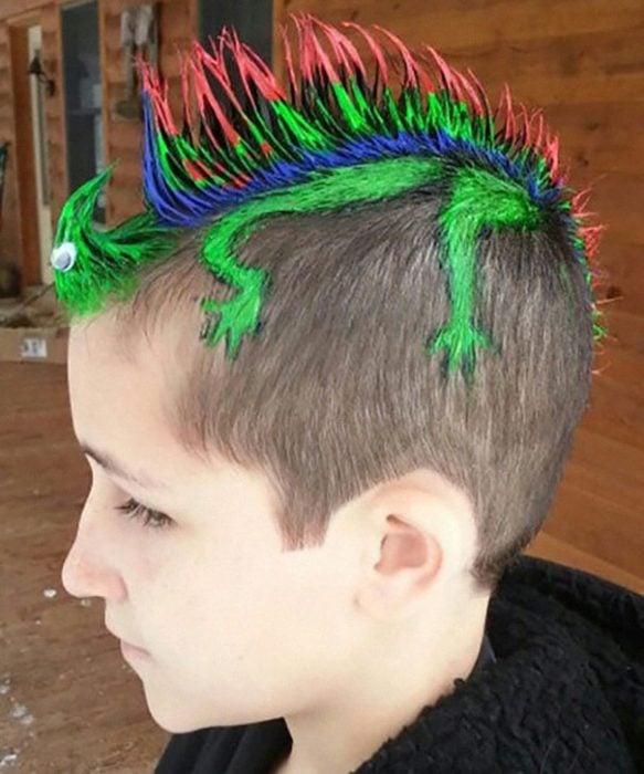 Niño con el cabello de colores simulando una iguana