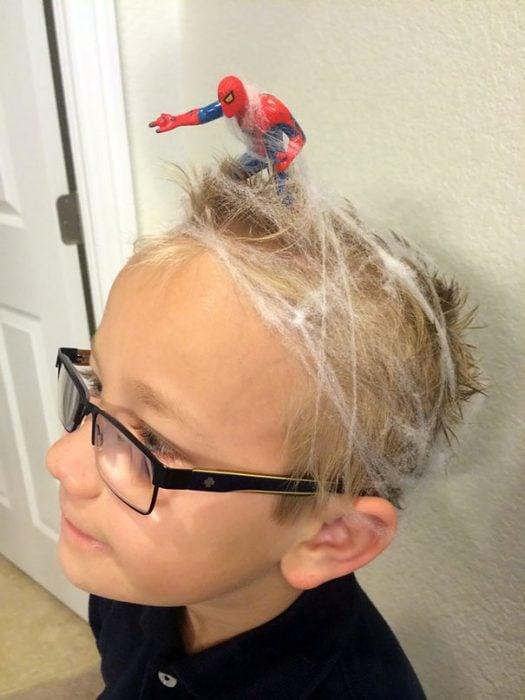 Niño con el cabello con telarañas y sobre el spiderman