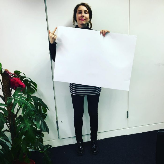 Chica sosteniendo una cartulina para el reto A4 challenge