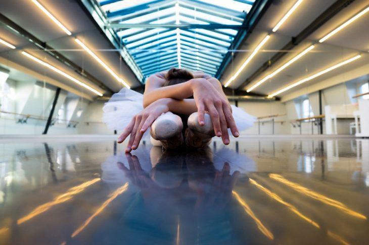 Bailarina de ballet sentada en el escenario