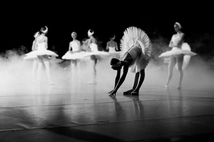 Bailarina de ballet agachada en el escenario