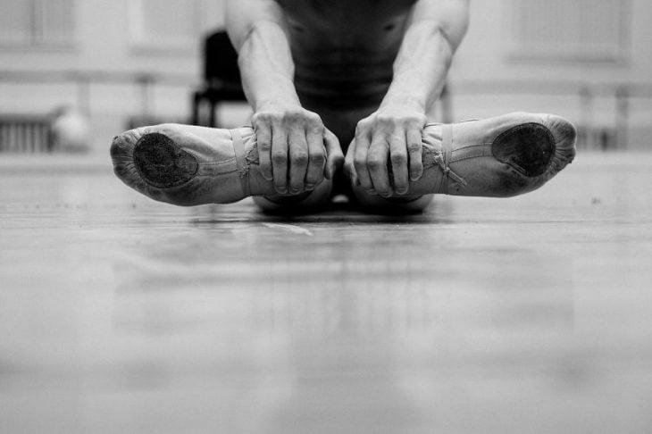 Bailarina de ballet tocando sus pies