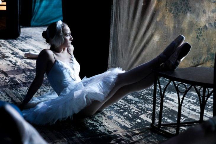Bailarina de ballet descansando sus pies sobre una silla