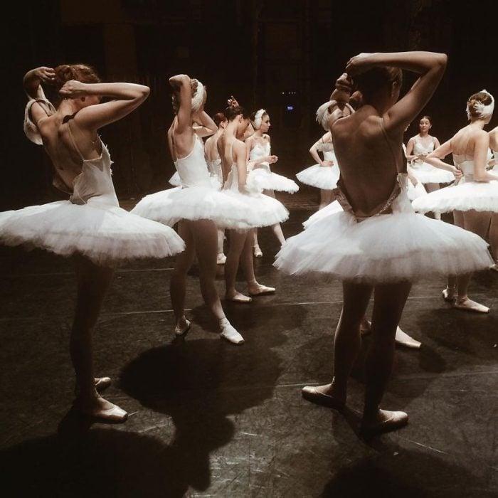 Bailarinas de ballet peinándose antes de entrar a una función