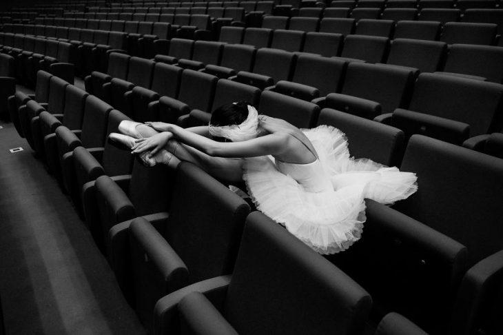 Bailarina de ballet descansando en una butaca del teatro