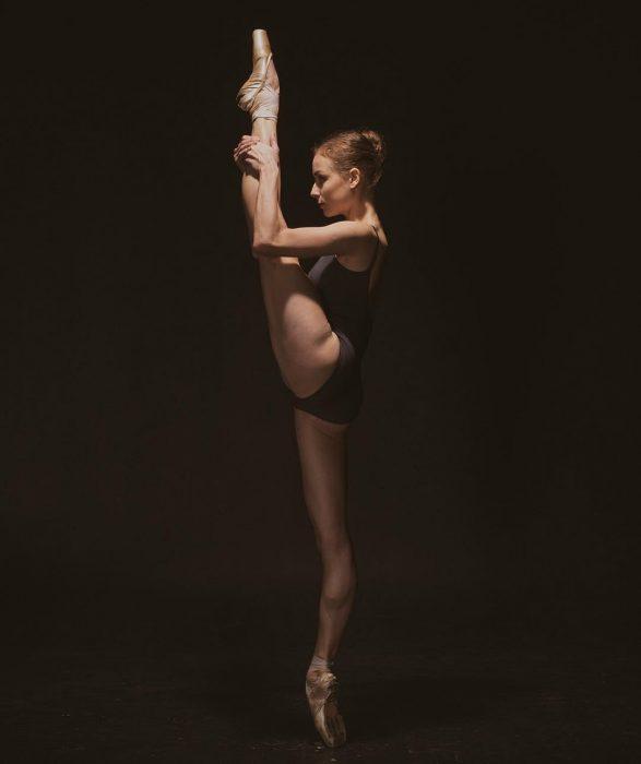 Bailarina de ballet con una pierna levantada sobre su cabeza