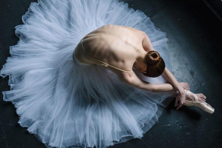 Bailarina de ballet descansando en el escenario