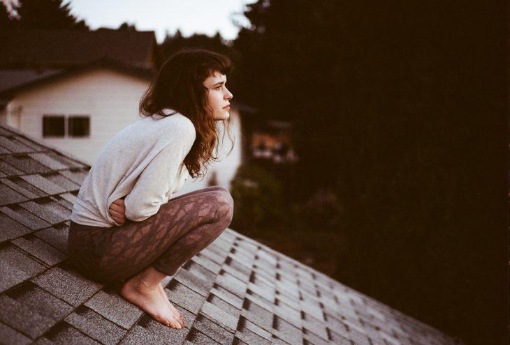 Chica sentada sobre el techo de su casa