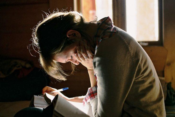 Chica triste escribiendo una carta