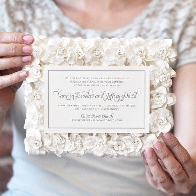 Invitación de boda sobre una cama de rosas artificiales