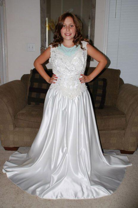 Niña usando el vestido de novia de su mamá desde que que nació para ver su desarrollo