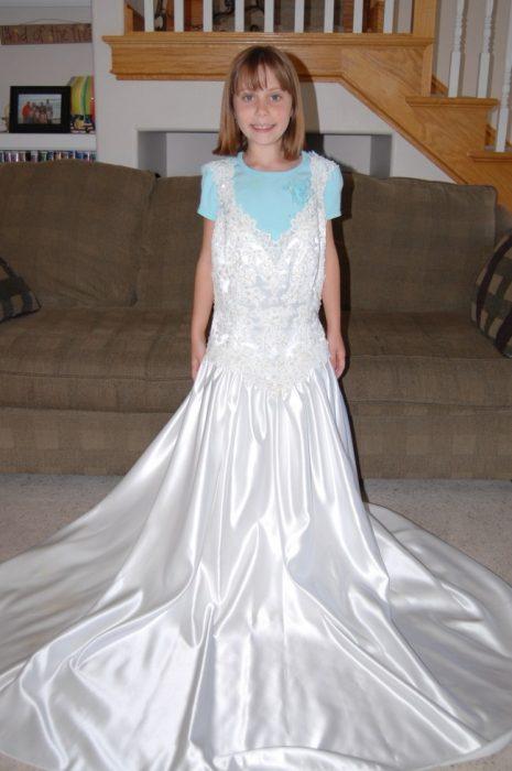 Niña usando el vestido de novia de su madre para ver su crecimiento