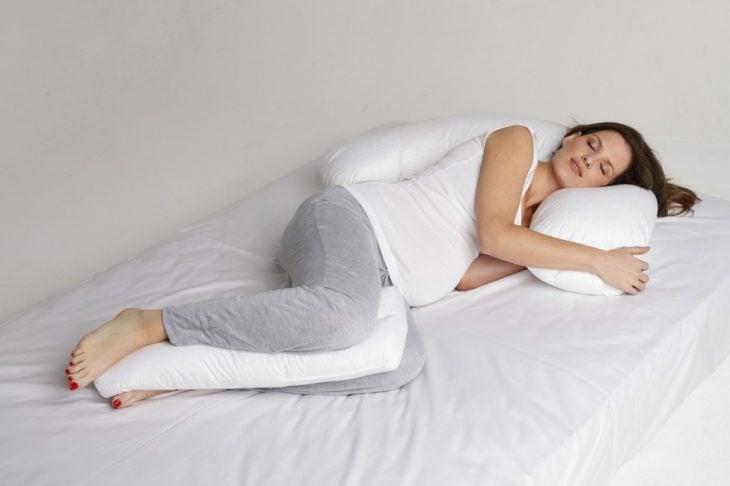 Chica embarazada durmiendo con una almohada ente sus piernas