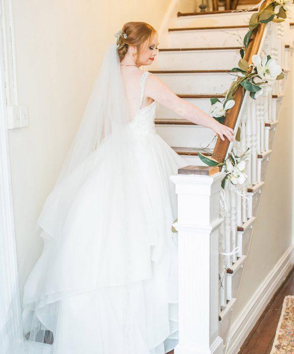 Modelo con síndrome de Down Madeline Stuart vestida de novia bajando por las escaleras