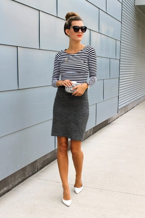 Girl wearing a gray pencil skirt and a black blouse with stripes