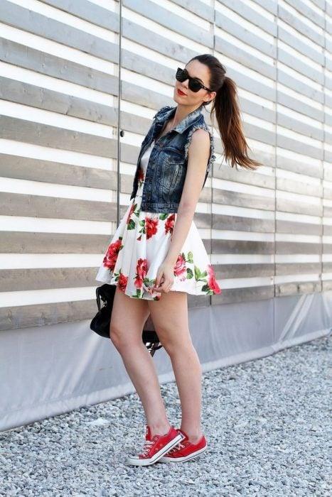 Outfit de oficina. Chica usando una falda de flores, chaleco y flats
