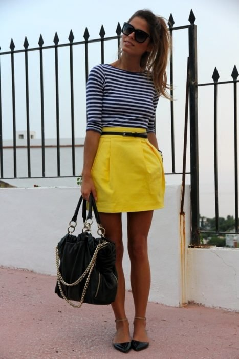 Office outfit. Girl wearing a yellow skirt, striped blouse and flats