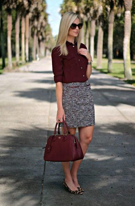 Outfits de oficina. Chica usando una falda de color gris y una blusa de color guinda